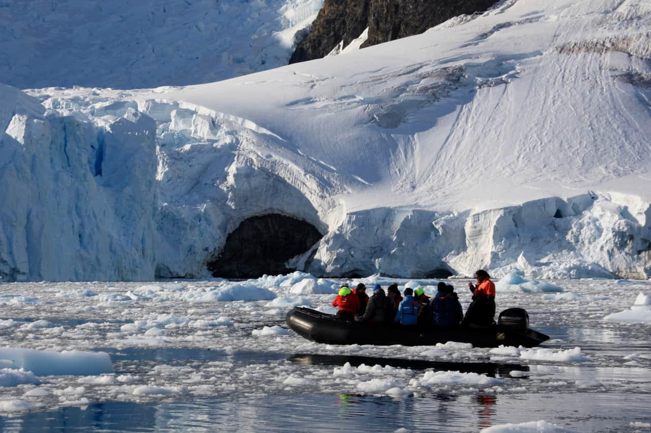 Travellers enjoy a zodiac cruise through the ice of Paradise Bay while visiting Antarctica.