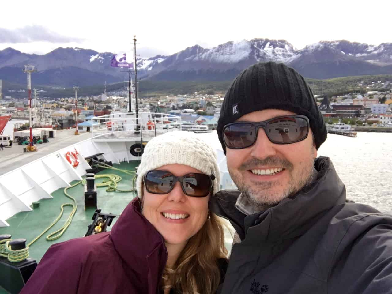 Happy couple aboard the expedition ship, MV Ushuaia, with the town of Ushuaia in the background.