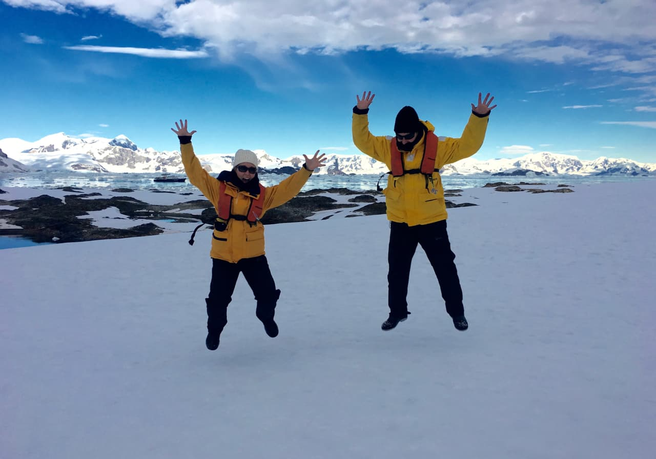 Couple dressed in yellow parkas jumping on the snow while visiting Antarctica.