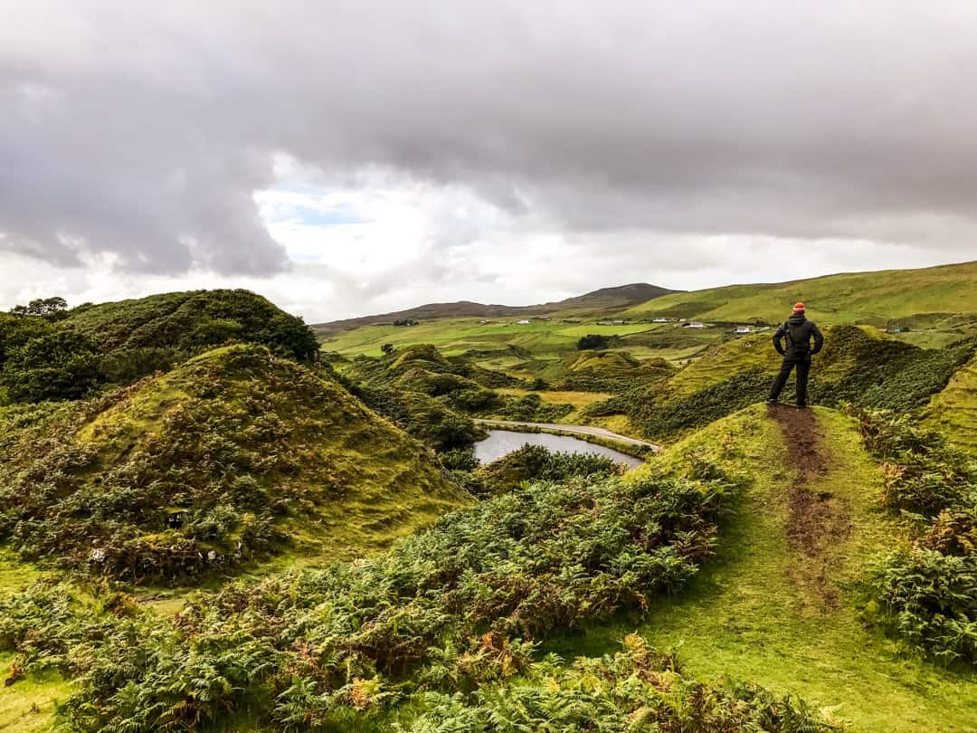 John stands on one of the small hills that scatter the Fairy Glen on Skye.
