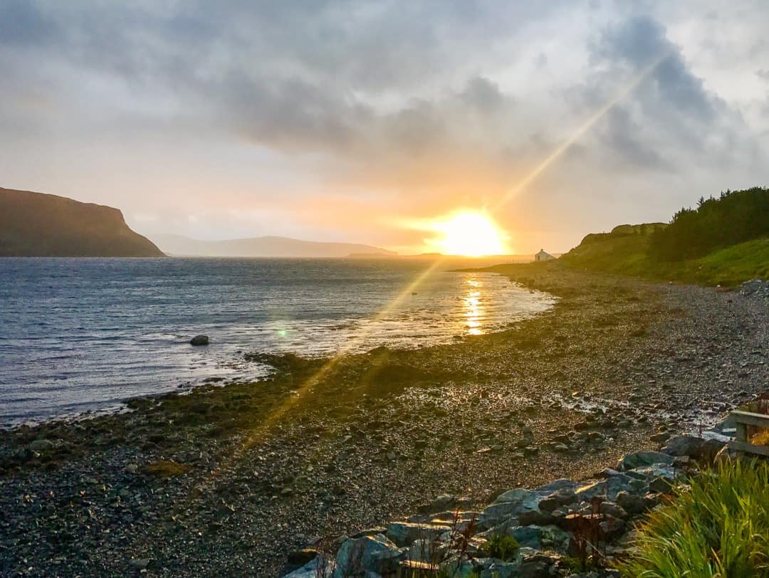 The sun breaks through clouds as it sets over Loch Bay on Skye.
