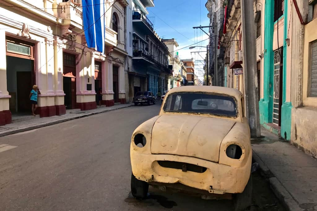 An old yellow car on a street scene in Havana, Cuba.
