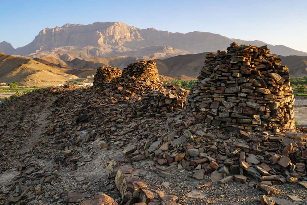 Oman photography – sunset slowly turns tombs of Al Ayn golden as the mountain backdrop enjoys the last light of the day.