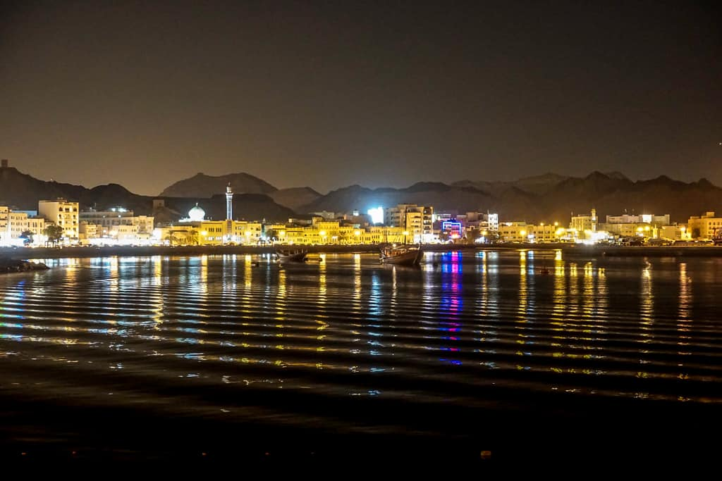 Oman city photos – Mutrah corniche at sunset complete with reflections across the harbour.