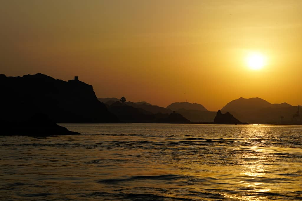 Oman photo gallery – a glorious sunset during a dhow cruise along the Gulf of Oman looking back towards a mountainous landscape dotted with fortresses.